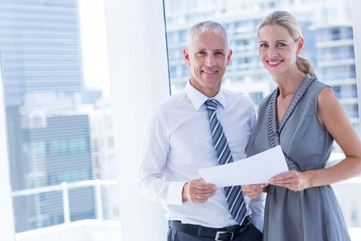 Smiling business people talking over a paper sheet
