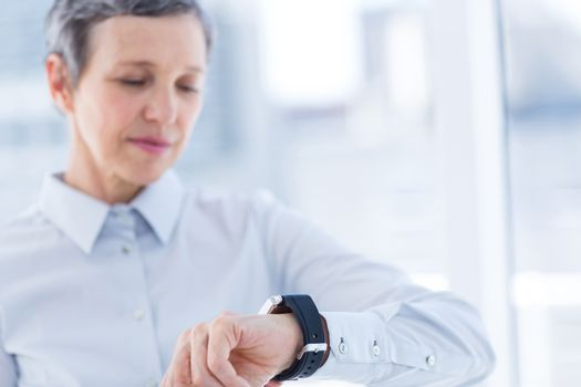 A businesswoman looking her smartwatch