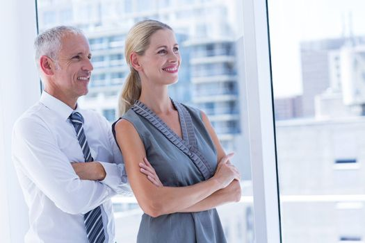Two smiling business people looking away