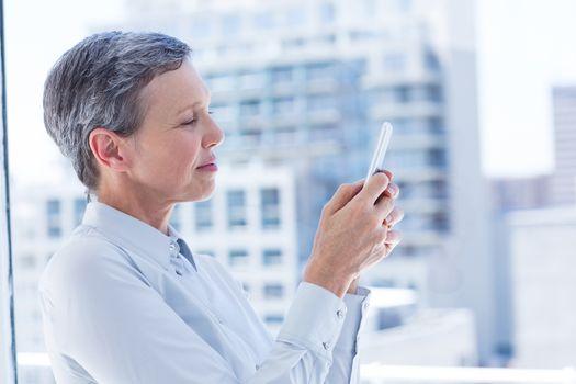Businesswoman sending a text message