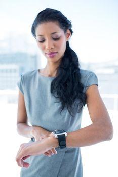 A businesswoman using her smartwatch