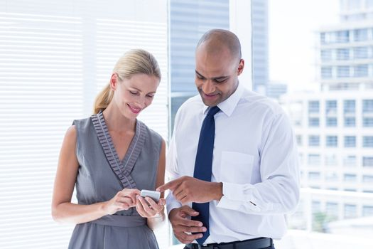 Businesswoman showing her phone to her colleague