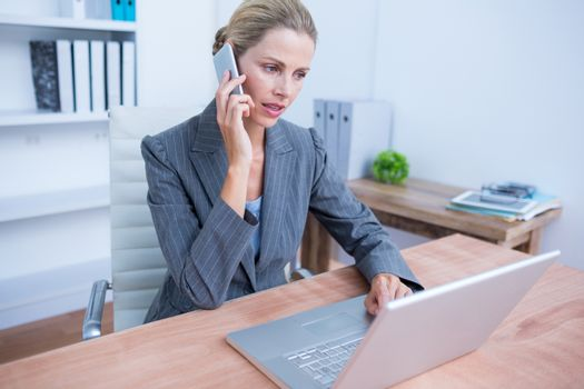Pretty blonde businesswoman phoning and using her laptop
