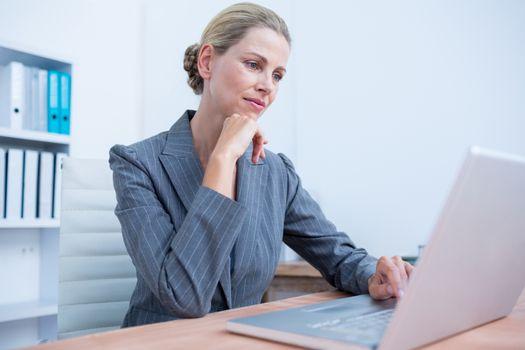 Pretty blonde businesswoman using her laptop