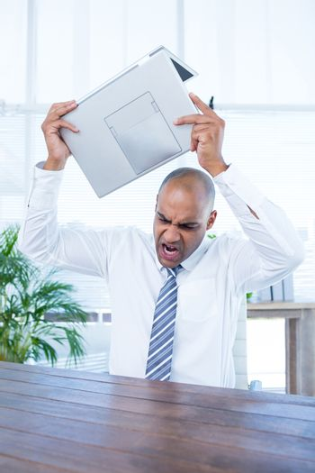 Irritated businessman about to break his laptop