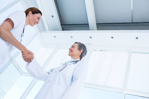 Smiling medical colleagues shaking hands