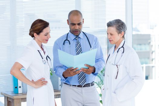 Concentrated medical colleagues analyzing file together