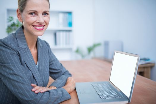 Smiling businesswoman in front of her laptop