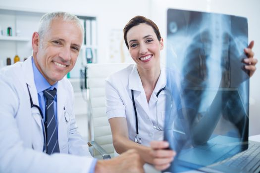 Portrait of smiling medical colleagues holding x-ray