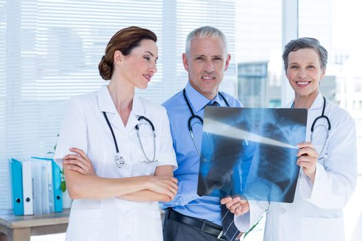 Portrait of smiling medical colleagues examining x-ray together