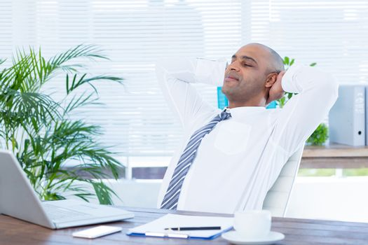 Relaxed businessman lying down in swivel chair