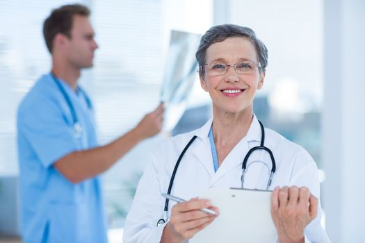 Smiling doctor holding a clipboard