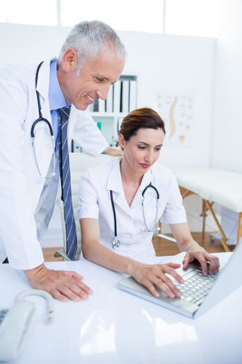 Smiling medical colleagues working with laptop