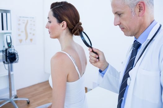 Doctor examining his patient back with magnifying glass