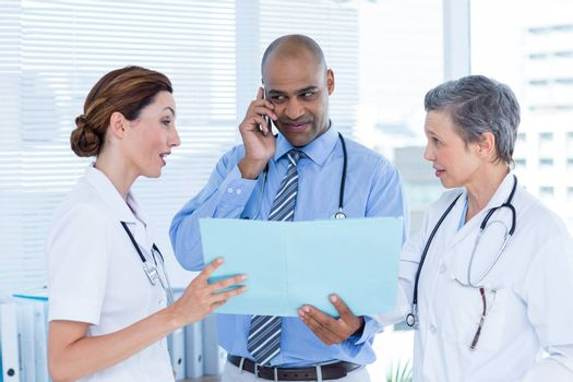 Concentrated doctor showing file to his colleagues while calling