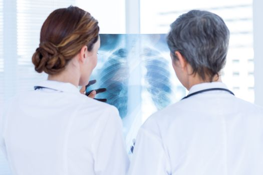 Rear view of concentrated medical colleagues examining x-ray together