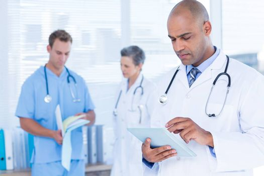 Attentive doctor using his tablet
