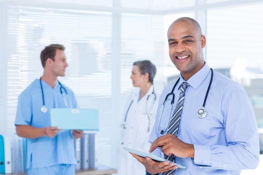 Smiling doctor using his tablet