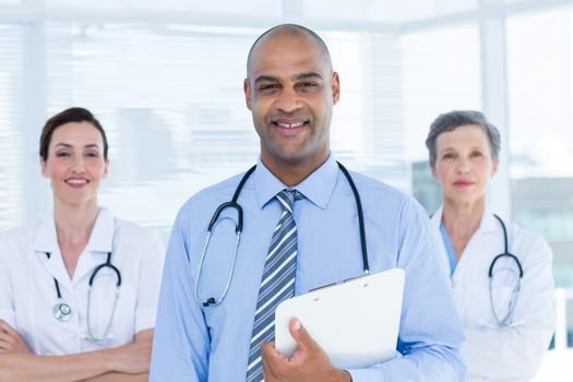 Portrait of smiling doctor holding file and standing in front of his colleagues