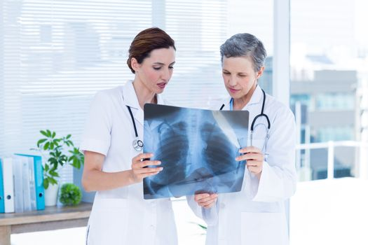 Concentrated medical colleagues examining x-ray together