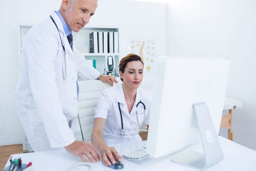 Concentrated medical colleagues working with computer