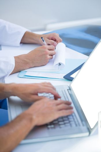 Medical colleagues working with laptop and taking notes