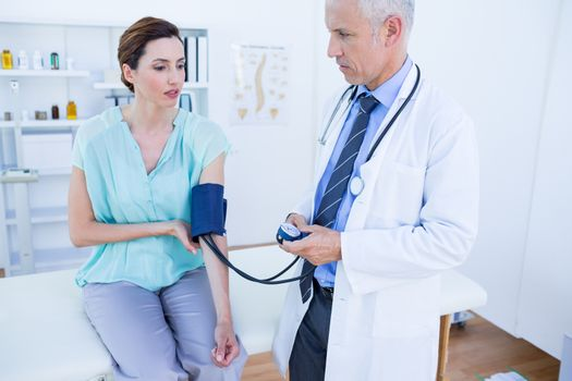 Doctor checking blood pressure of a young woman