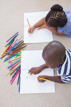 Siblings on the floor drawing