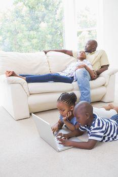 Happy siblings using their laptop