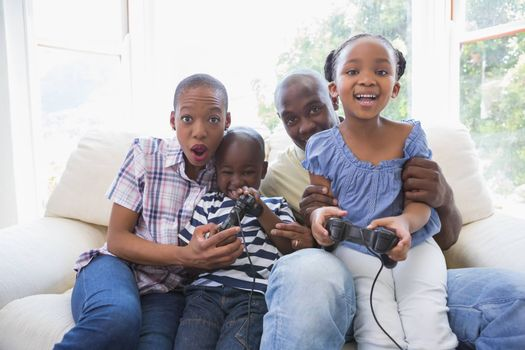 Happy smiling family playing video games together