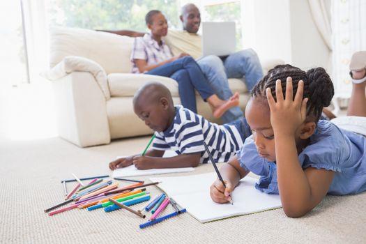 Happy siblings on the floor drawing
