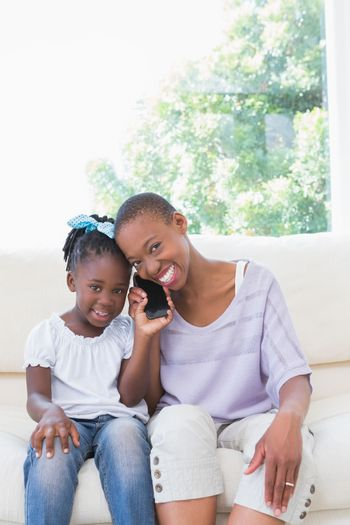 Portrait of a happy smiling mother phoning with her daughter on couch