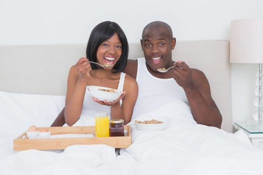 Portrait of a pretty couple taking breakfast in bed together
