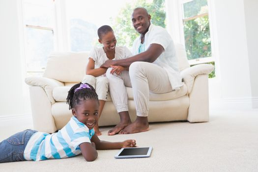Pretty couple sitting on couch and their daughter using digital tablet