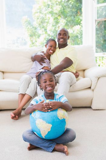 Portrait of a happy smiling couple sitting on couch and daughter taking a globe