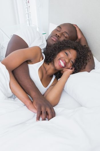 Happy smiling couple in bed