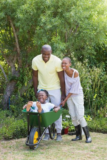 Happy smiling couple playing with wheelbarrow and their son