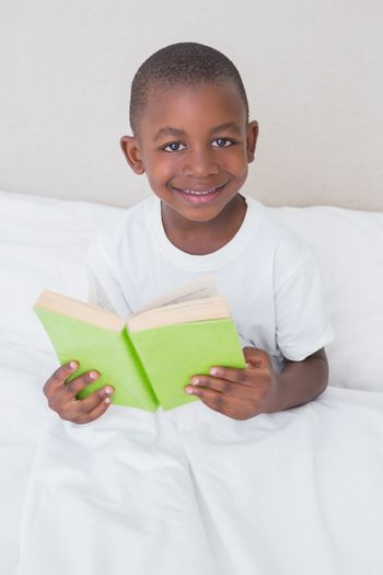 Portrait of a little boy reading book in bed