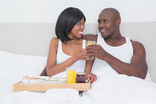 Pretty couple taking breakfast in bed together