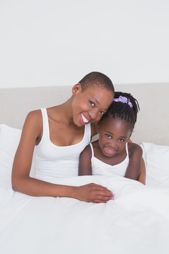 Portrait of a pretty mother with her daughter in bed