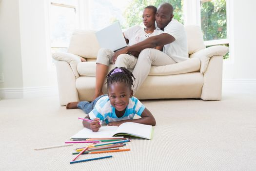 Pretty couple using laptop on couch and their daughter drawing