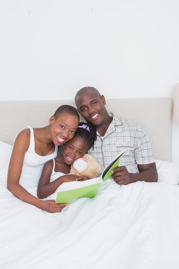 Portrait of a pretty couple reading a book with their daughter in bed
