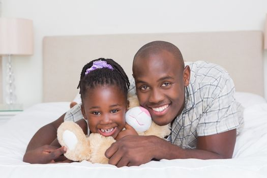 Pretty little girl with his father in bed
