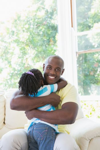 Happy smiling father to hug with her daughter in couch