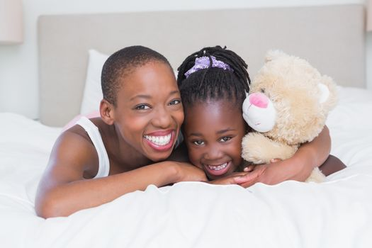 Portrait of a pretty beautiful smiling mother with her daughter in her bed