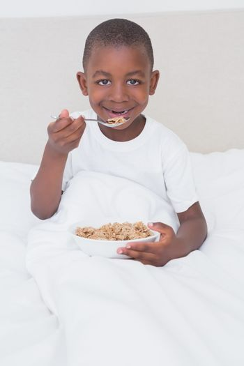 Portrait of a pretty little boy eating cereals in bed