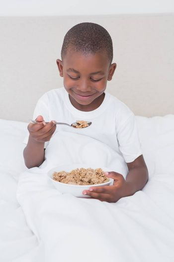 Pretty little boy eating cereals in bed