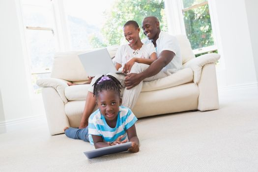 Pretty couple using laptop on couch and their daughter using tablet