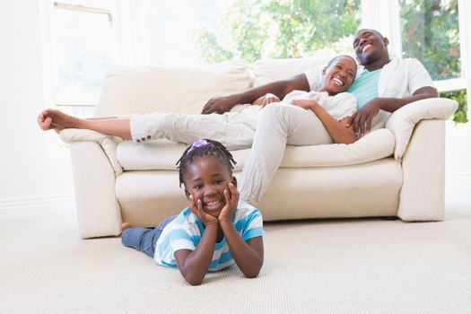 Portrait of a pretty couple sitting on couch and their  daughter looking at camera
