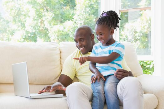 Happy smiling father using laptop with her daughter on couch